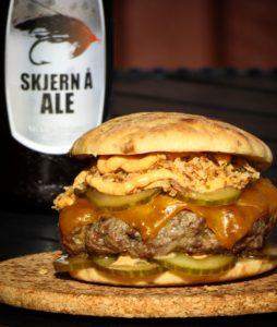 Burger im Hot-Dog-Stil mit eingelegten Gurkenscheiben, Röstzwiebeln und Cheddar